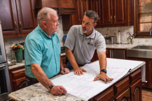 Thomas Building Company owner Drew Gasser looking at document with a client